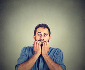 Photo Portrait anxious young man biting his nails fingers freaking out
