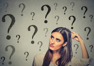 confused thinking woman scratching her head looking up at many question marks