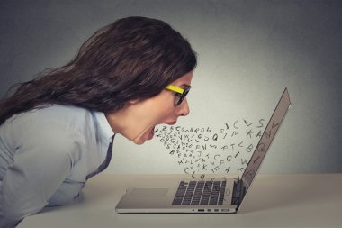 Angry furious businesswoman working on computer, screaming
