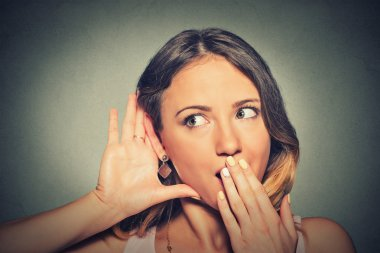 surprised young nosy woman hand to ear gesture carefully secretly listening