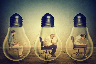company employees sitting in row inside electric lamp using working on computer