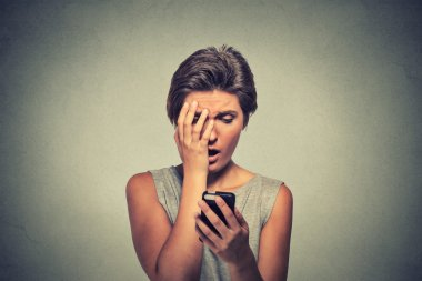 stressed woman holding cellphone disgusted shocked with message she received