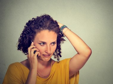 Portrait unhappy young woman talking on mobile phone looking down stressed isolated on gray wall background. Human face expression, emotion, bad news reaction stock vector