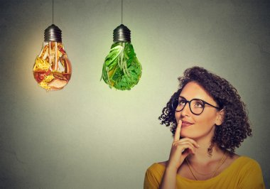 woman thinking looking up at junk food and green vegetables shaped as light bulb
