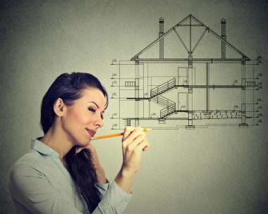 Happy young woman drawing new house plan with pencil