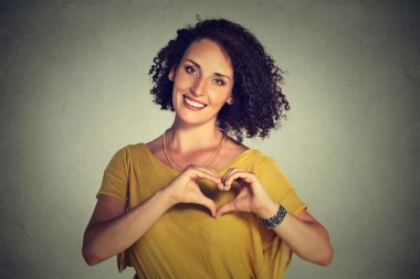 smiling cheerful happy young woman making heart sign with hands