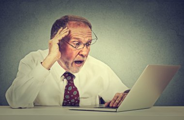 Closeup portrait anxious senior man looking at laptop screen seeing bad news or photos with disgusting emotion on his face isolated on gray office wall background. Human emotion, reaction, expression stock vector