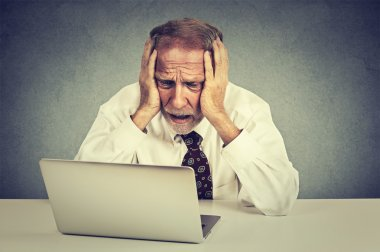 senior stressed man working on laptop sitting at table isolated on gray wall background