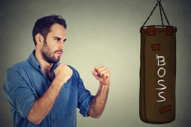 man ready to punch boxing bag with boss written on it. Employee employer relationship concept