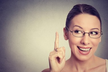 portrait happy beautiful woman looking up pointing finger at blank copy space