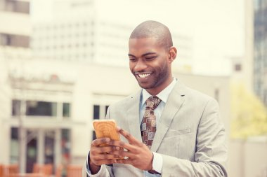 Young happy smiling urban professional man using smart phone outdoors