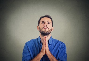 handsome man praying hands clasped hoping for best asking for forgiveness