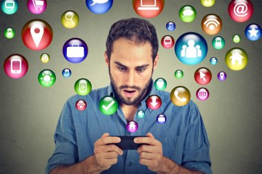 Shocked man using texting on smartphone application icons flying out of cellphone