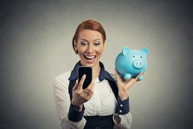 happy young woman holding piggy bank looking at smart phone