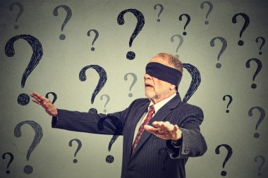business man blindfolded stretching his arms out walking through many questions