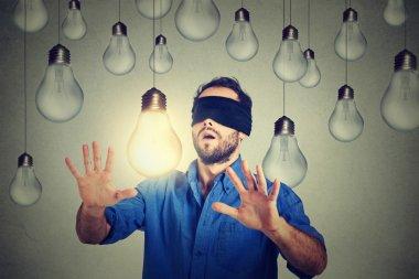 Blindfolded man walking through lightbulbs searching for bright idea
