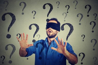 Portrait business man blindfolded stretching his arms out walking through many questions