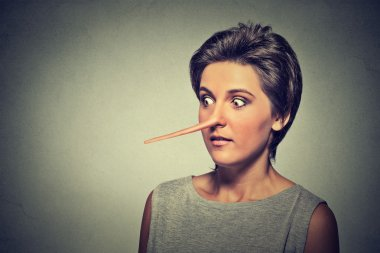 Woman with long nose isolated on grey wall background. Liar concept