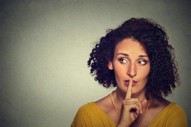 secretive woman placing finger on lips asking shh, quiet, silence looking sideway