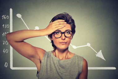 Stressed shocked woman in glasses with financial market chart graphic going down