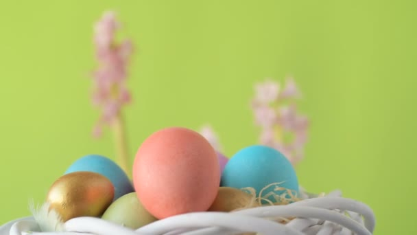 Colourful Easter eggs of pink, golden and green colour lie in straw spinning around on blurred light green background with pink and magenta hyacinth flowers. Spring Christian holidays design concept