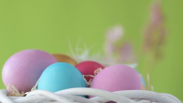 Barevná velikonoční vajíčka růžové, zlaté a zelené barvy leží na rozmazaném světle zeleném pozadí s růžovými a fialovými květy hyacintu. Koncept návrhu jarních křesťanských svátků