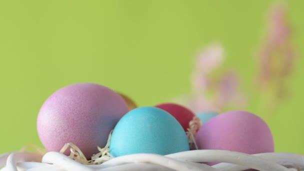 Rózsaszín, arany és zöld színű húsvéti tojások szalmában forognak a homályos világoszöld háttér körül rózsaszín és bíbor jácint virágokkal. Tavaszi keresztény ünnepek design koncepció