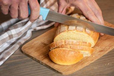 "Картина, постер, плакат, фотообои ""человек режет хлеб зазубренным ножом."", артикул 445508068"