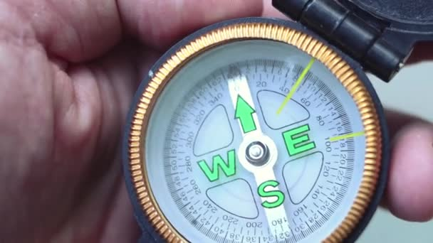 Man holds a compass in hand and looks for direction