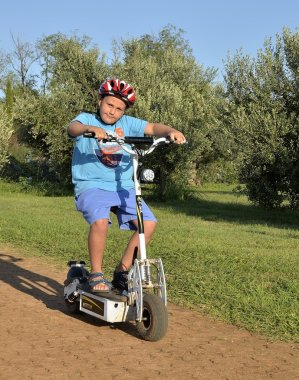 Child plays with electric scooter. Monopattino, segway.