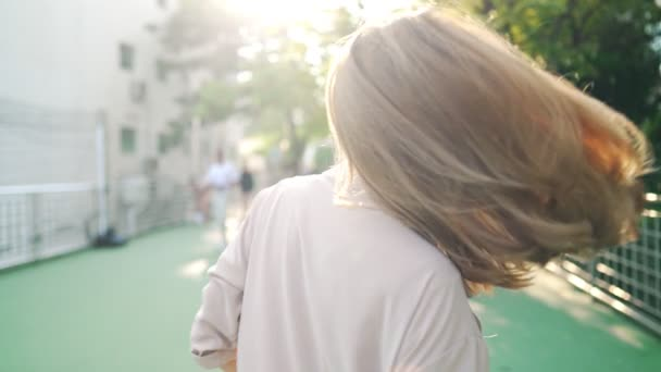 Closeup young cheerful female in city overpass park scene, beautiful woman with long faded blonde hair spins around herself happily, sun flare illuminate, slow motion video nature and beauty, environmental conservation or issues, relaxing exercise