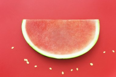 Slice of watermelon without seeds on red background