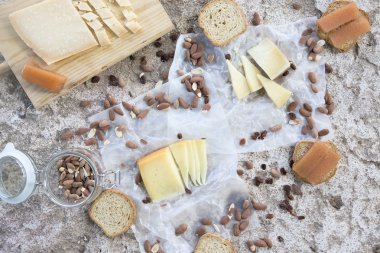Variety of cheeses, roasted almonds, toasts and quince on stone table
