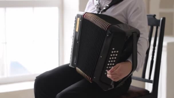 A young man in a white shirt and black trousers plays the accordion.Close-up, slow motion.