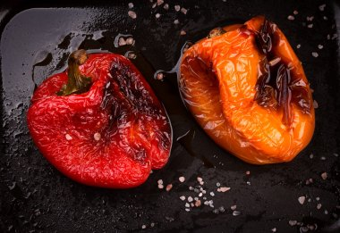 Tasty roasted red and orange bell peppers in pan