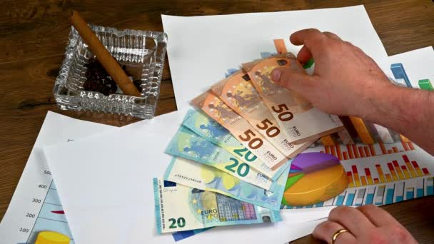 hands of man handling euro banknotes of different denominations