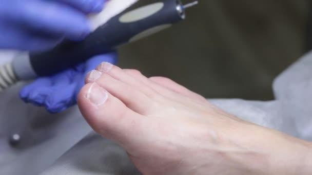 Der Nageltechniker reinigt nach der Verarbeitung mit dem Cutter den Staub von den Nägeln. Medizinische Pediküre im Salon.