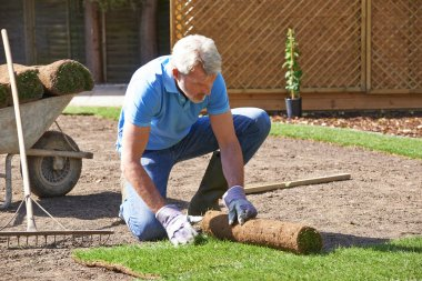 Gardener Laying Turf For New Lawn