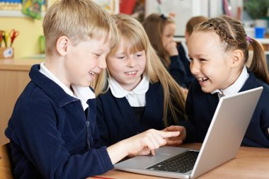 Group Of Elementary School Children Working Together In Computer