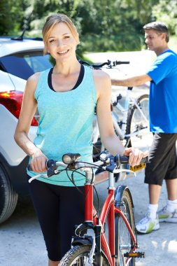 Mature Couple Taking Mountain Bikes From Rack On Car