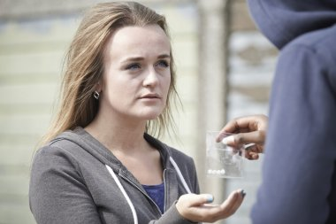 Teenage Girl Buying Drugs On The Street From Dealer
