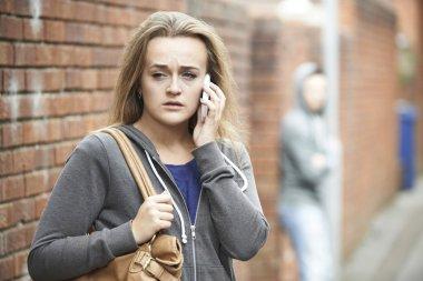 Teenage Girl Using Phone As She Feels Intimidated On Walk Home