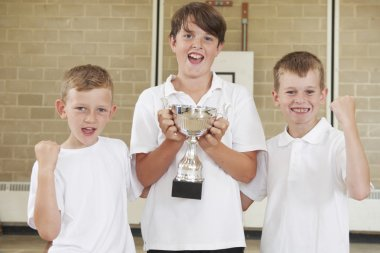 Male School Sports Team In Gym With Trophy
