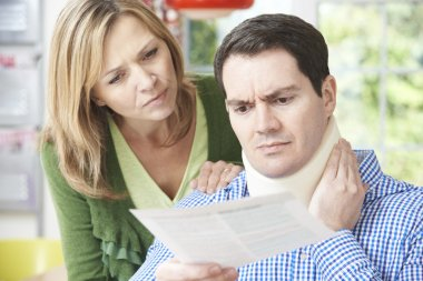 Couple Reading Letter In Respect Of Husband's Neck Injury