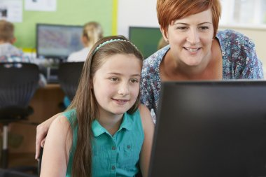 Female Elementary Pupil In Computer Class With Teacher