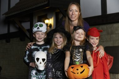 Halloween Party With Children Trick Or Treating In Costume With