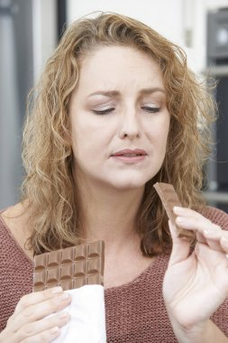 Guilty Woman On Diet Eating Chocolate Bar At Home