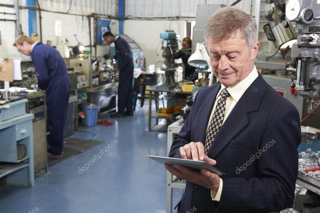 Owner Of Engineering Factory Using Digital Tablet With Staff In