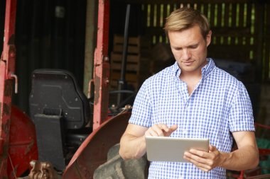 Farmer Holding Digital Tablet Standing In Barn With Old Fashione