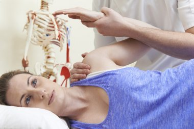 Male Osteopath Treating Female Patient With Shoulder Problem